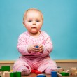 Infant girl playing in room on wooden floor — Stock Photo #9447567