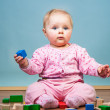 Infant girl playing with bricks — Stock Photo #9447572