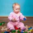 Infant girl playing with bricks — Stock Photo #9447576