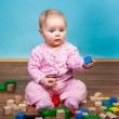 Infant girl playing in room on wooden floor — Stock Photo #9447578