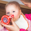 Mother feeding infant girl with a tea bottle — Stock Photo #9447585