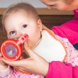 Mother feeding infant girl with a tea bottle — Stock Photo #9447588