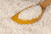 Rice in a discolored wooden spoon — Stock Photo