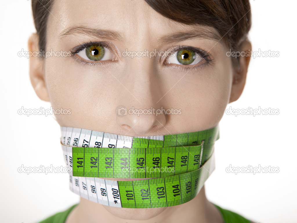 Portrait of a young  woman with a green measuring tape covering the mouth — Stock Photo #8536867