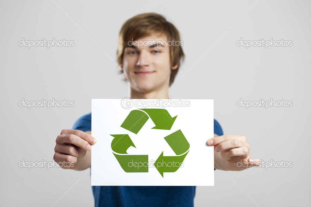 Casual young man holding a recycling sign to promote a green and better world, over a gray background — Stock Photo #9727872