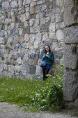 Девушка у каменной стены — Stock Photo