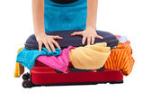 Woman crammed full of clothes in red suitcase — Stockfoto