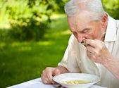 Uomo anziano mangia — Foto Stock