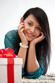 Woman on the floor with gift box — Stock Photo