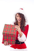 Mrs. Santa opening a gift box — Stock Photo