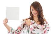 Mladá žena, ukázal na prázdnou kartu v ruce — Stock fotografie