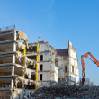 Demolition of a building with excavator - Stock Photo