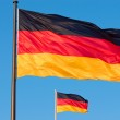 Two german flags flying in the wind — Stock Photo #9249301