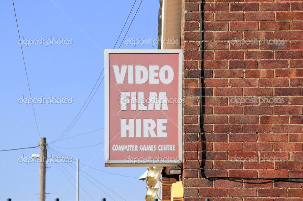 Old faded sign hanging on brick wall advertising video film hire and computer games centre — Stock Photo #9221733