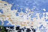 Blue paint peeling brick wall — Stock Photo
