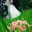 Wedding bouquet of roses laying in grass against enamoured pair — Stock Photo