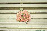 Beautiful bouquet of roses lie on a bench — Stock Photo
