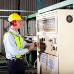 Industrial technician writing down machine setting figures — Stock Photo
