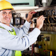Electrician working on industrial machine - Stock Photo