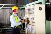 Técnico industrial, anotando números de configuração de máquina — Foto Stock