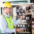 Electrician checking machine control box temperature — Stock Photo