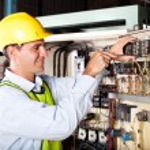 Electrician repairing industrial machine — Stock Photo