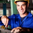 Happy mechanic repairing machine — Stock Photo