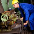 Machinist operating machine tool - Stock Photo