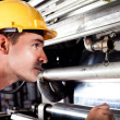 Industrial machine operator checking on machine while it's running — Stockfoto