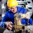 Technician fixing industrial sewing machine — Stock Photo