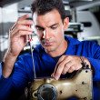 Mechanic repairing industrial sewing machine — Stock Photo