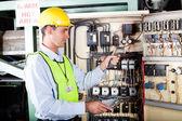 Electrician checking machine control box temperature — Stock Photo