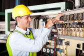 Electrician repairing industrial machine — Stock Photo