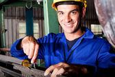 Happy mechanic repairing machine — Stock Photo