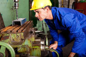 Machinist operating industrial drilling press — Stock Photo