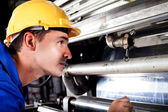 Industrial machine operator checking on machine while it's running — Foto de Stock
