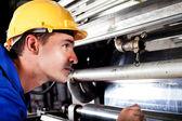 Industrial machine operator checking on machine while it's running — Stock Photo
