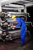 Printer operating industrial printing machine — Stock Photo