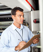 Industrial technician taking machine readings — Stock Photo