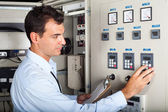 Industrial engineer adjusting machine settings — Stok fotoğraf