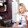 Stock Photo: Young woman calculating credit card bill
