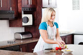 Young woman making fruit salad — Stock Photo