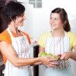 Teen girl helping mother in kitchen — Stock Photo