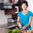 Middle aged woman cooking - Stock Photo