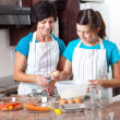 Mother teaching teen daughter baking — Stockfoto