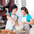 Teen daughter helping mother in kitchen — Stockfoto