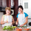 Middle aged woman cooking with senior mother — Stock Photo #10253798