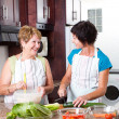 Senior mother and middle aged daughter cooking - Stockfoto
