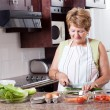 Elderly woman cooking — Stock Photo