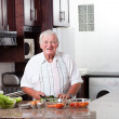 Senior man preparing food — Stock Photo